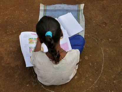 Una niña, que se ha perdido sus clases en Internet debido a la falta de conexión, se sienta en el suelo dentro de un círculo para mantener una distancia segura mientras escucha lecciones pregrabadas, en Dandwal, Maharashtra (India).