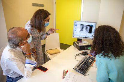 La neumóloga Alba Esperanza muestra a Manuel Pedrosa y Carmen Lavín una de sus radiografías.