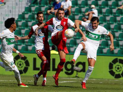 El delantero del Celta Iago Apsas disputa el balón con los jugadores del Elche.