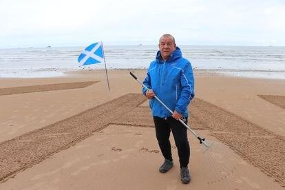 Dougie Bogie escribe con un rastrillo las letras del partido Alba, en la playa de Aberdeen.