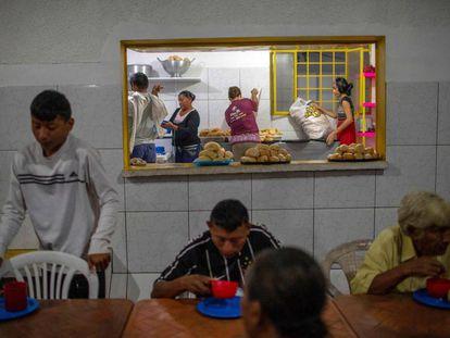 Varios venezolanos desayunan ayer en una parroquia en Pacaraima.