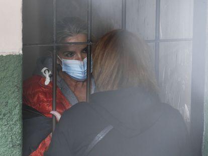 De pie tras las rejas, la expresidenta interina de Bolivia, Jeanine Áñez, habla con una mujer no identificada en la cárcel de una comisaría de policía, en La Paz, Bolivia.