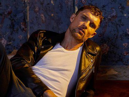 El actor Ed Skrein luce chaqueta de cuero y pantalón de CH Carolina Herrera, camiseta Abanderado y cadena de Great Frog.