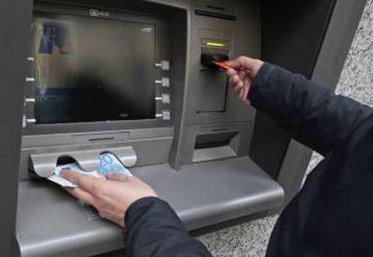Una persona saca dinero de un cajero en Madrid