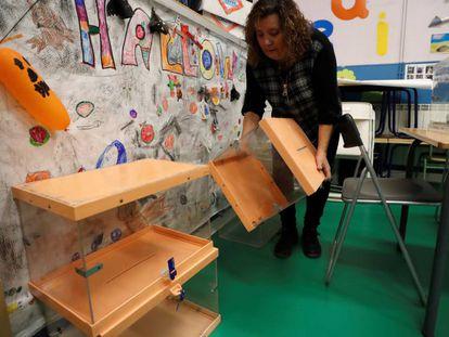 Una mujer coloca urnas electorales en un colegio para las generales de noviembre de 2019.