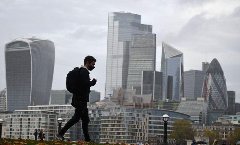 Un hombre camina en Londres con las torres de la City al fondo, el 1 de noviembre.