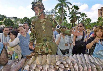 Un militar venezolano vende pescado en uno de los mercados organizados por el Gobierno de Chávez.