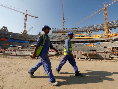 Dos trabajadores en el interior del estadio Lusail de Doha, Qatar, en diciembre de 2019. El recinto se ha construido para el campeonato mundial de fútbol de 2022, que se celebrará en esta ciudad.