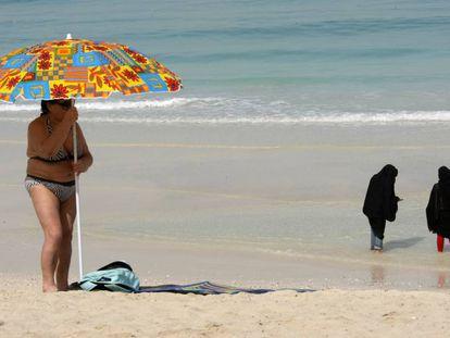 Una turista coloca una sombrilla mientras dos mujeres se mojan los pies en una playa de Dubái.
