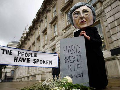 Opositores del Brexit llevan puesto un careto de la primera ministra, Theresa May, este viernes en Londres.