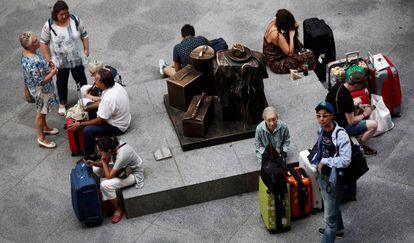 Una decena de viajeros espera en la estación de Atocha de Madrid.