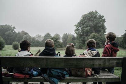 Cinco niños sentados miran al horizonte.
