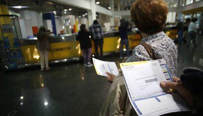 Usuarios hacen cola en una oficina de Correos.