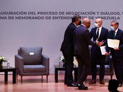 El jefe de la oposición y un delegado del Gobierno venezolano se saludan tras las reuniones en Ciudad de México.