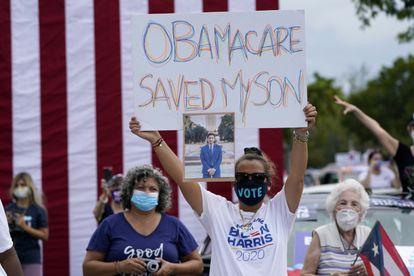 """La venezolana Adelys Ferro sostiene una pancarta en la que se lee """"Obamacare salvó a mi hijo"""" en un evento de campaña de Joe Biden en Miami."""