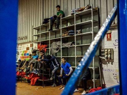 Varios niños marroquíes duermen en estanterías dentro de una nave industrial del Tarajal, Ceuta, el pasado martes.