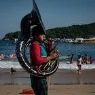 Un músico toca una canción para los turistas en la playa de Caleta el 09 de Agosto de 2020