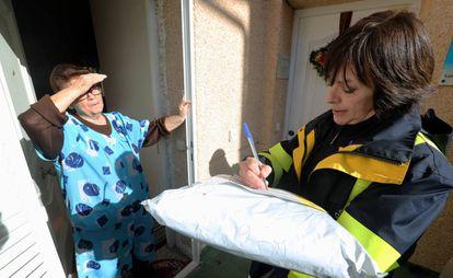 La cartera Cristina García entrega un paquete a la vecina Inocencia Prieto, de 78 años.