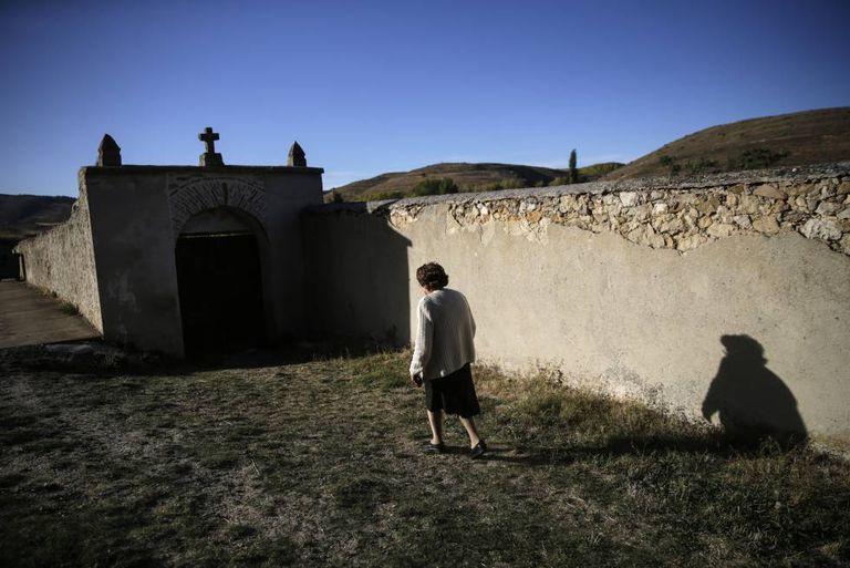 Una mujer se dirige al cementerio del municipio de Alustante, en Guadalajara.