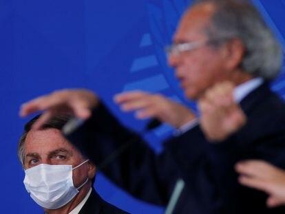El presidente Jair Bolsonaro mira a su ministro de Economía, Paulo Guedes, durante una ceremonia en Brasilia.
