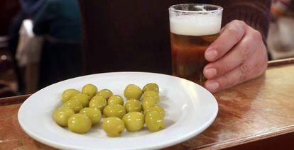 Un cliente ante una caña de cerveza y un plato de aceitunas en un bar de Madrid.