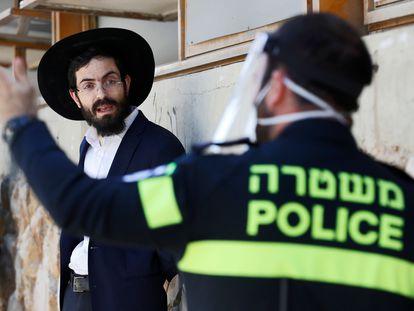 Un policía con mascarilla desaloja a un ultrarreligioso de un centro de estudios rabínico, el jueves en Bnei Brak, en la periferia sur de Tel Aviv (Israel).