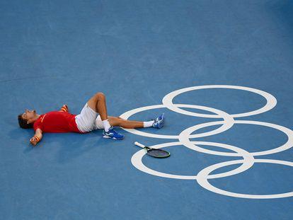 Carreño celebra su triunfo contra Djokovic tendido sobre la pista principal de Tokio.