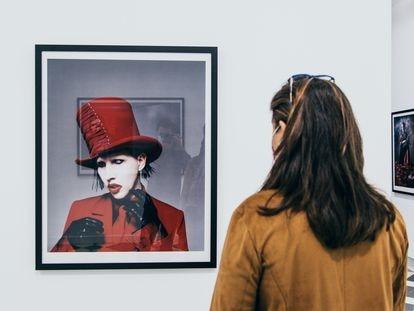 Una mujer observa uno de los retratos de Marilyn Manson en la exposición '21 años en el infierno' en La Térmica, en Málaga.