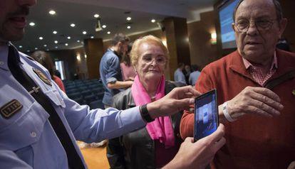 Un Mosso d'Esquadra escanea con su móvil el código QR de la pulsera para identificar a enfermos de Alzheimer en caso de que se pierdan.