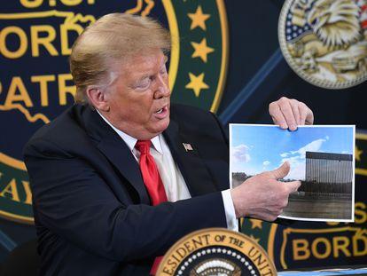 Trump muestra una foto del nuevo muro, este martes en Yuma, Arizona.