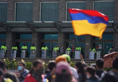 Manifestantes frente a la Fiscalía, custodiados por policías, en Bogotá.