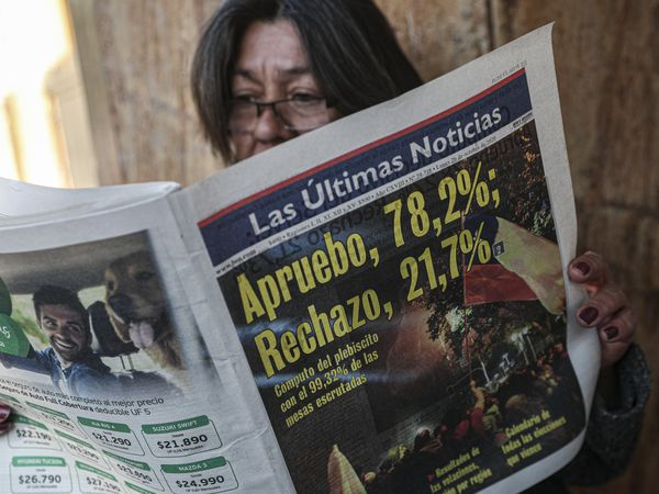 A woman reads a newspaper showing the results of the previous day's referendum in favor of rewriting the nation's constitution in Santiago, Chile, Monday, Oct. 26, 2020. Amid a year of contagion and turmoil, Chileans turned out Sunday to vote overwhelmingly in favor of having a constitutional convention draft a new charter to replace guiding principles imposed four decades ago under the military dictatorship of Gen. Augusto Pinochet. (AP Photo/Esteban Felix)