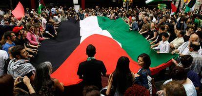 Manifestantes portan una gran bandera palestina en la protesta en  frente a la Cámara de Comercio israelí en Barcelona.
