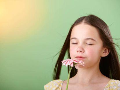 Una niña huele una flor.