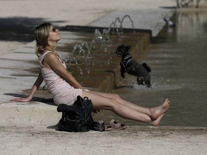 Una mujer y su perro se refrescan en una fuente en Zaragoza.