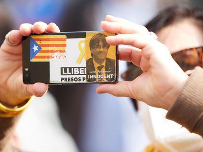 Una mujer toma una foto durante una manifestación, en la que exhibe una pegatina del expresidente Carles Puigdemont