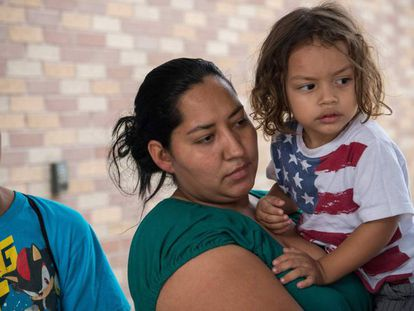 Una hondureña solicitante de asilo, sujeta a su hijo, con una camiseta de la bandera de Estados Unidos, en Texas.
