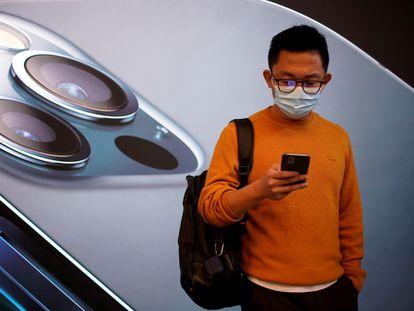 Un joven consulta su iPhone 12 frente a una tienda de Apple en Shanghái.