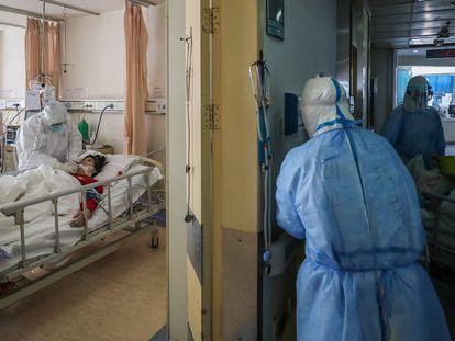 Personal sanitario atiende a una enferma en un hospital de Wuhan. En el vídeo, declaraciones de Tedros Adhanom, este viernes.