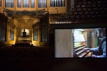 Benjamin Alard durante su recital. A la derecha, la pantalla instalada sobre el escenario en la que pueden verse de cerca las evoluciones de las manos y los pies del organista.