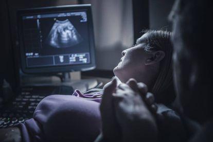 Dos padres miran con atención la ecografía de su futuro bebé.