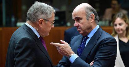 El ministro de Economía, Luis de Guindos, conversa con el director del MEDE en Bruselas.