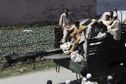 Paquistaníes subidos a bordo de un camión que transporta los restos de un helicóptero del ejército de EEUU que se estrelló durante la operación.