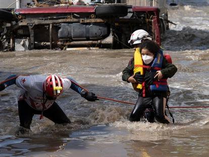 Una niña es auxiliada por rescatistas de la Cruz Roja debido a la orden de evacuación en la zona centro de Tula.