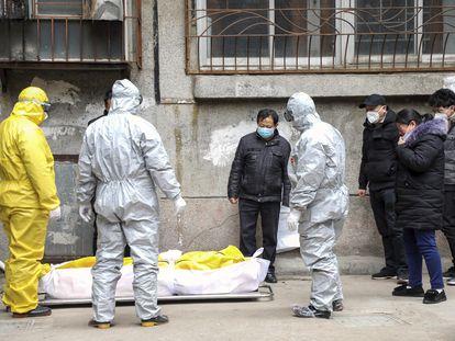 Un grupo de trabajadores sanitarios transporta el cuerpo de un fallecido con covid-19, en febrero en Wuhan (China).