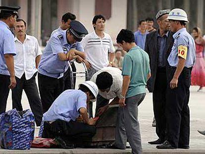 Policías chinos registran las maletas de ciudadanos uigures en Kashgar, en la región de Xinjiang.