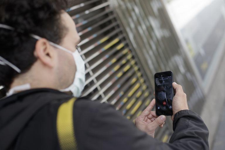 Un hombre protegido con mascarilla realiza una videollamada por su teléfono móvil, una de las formas más habituales de comunicarse durante la pandemia.