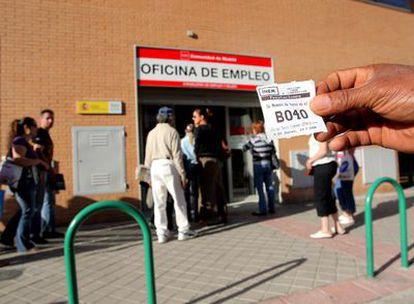 Un hombre enseña un tique con su número de turno delante de la oficina del Inem de la calle de la Virgen del Puig.