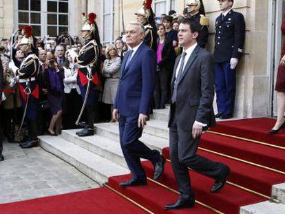 El ex primer ministro Jean-Marc Ayrault (i) y el nuevo jefe de Gobierno, Manuel Valls, este martes en París.