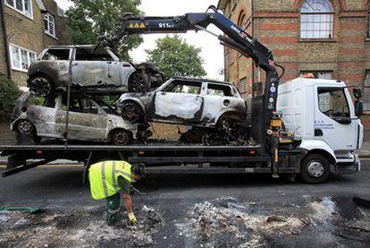 Empleados municipales retiran varios coches quemados en el barrio de Hackney.